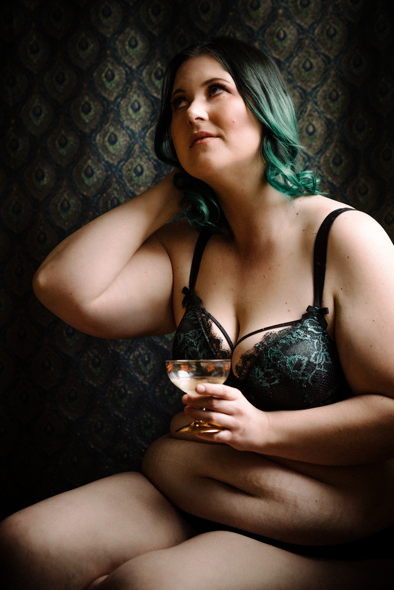 Boudoir photo of a lady with green hair against a peacock backdrop