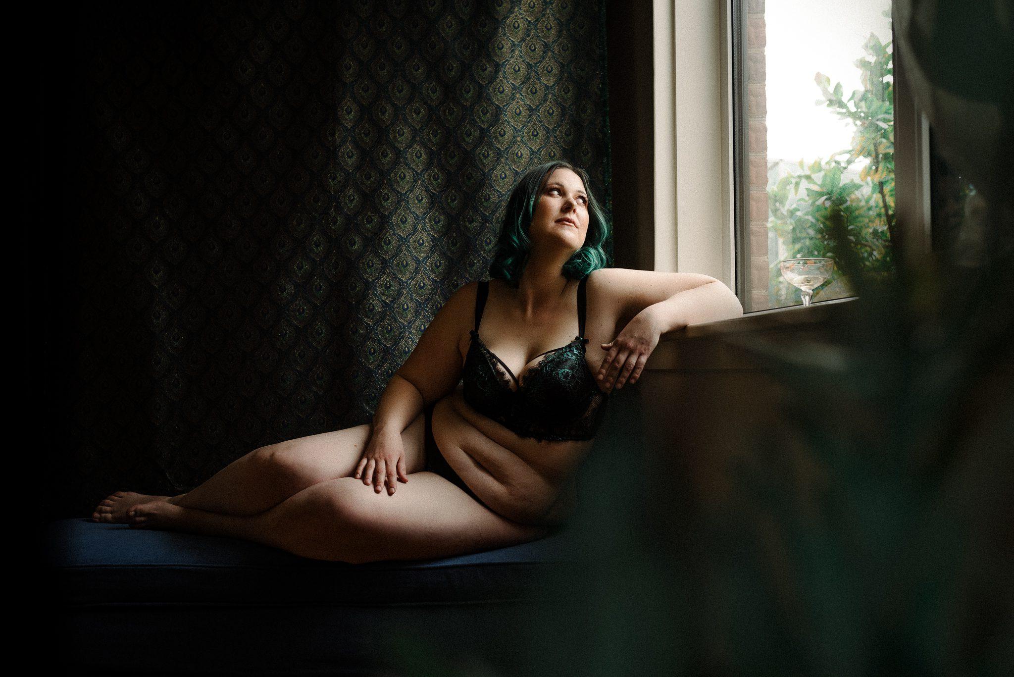 Boudoir portrait of a lady looking by a window