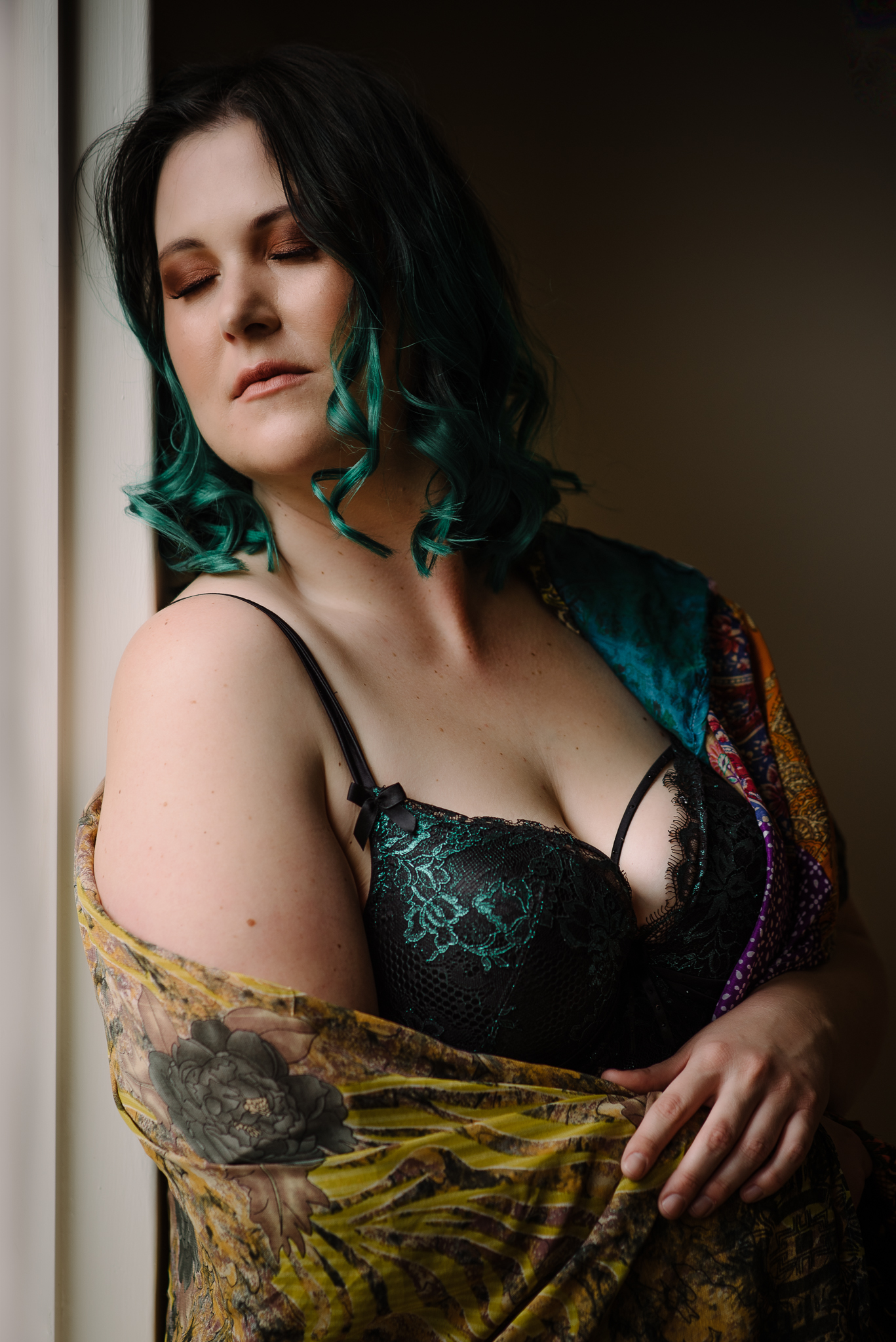 Boudoir portrait of a lady with green hair and bra, wrapped in a bright shawl